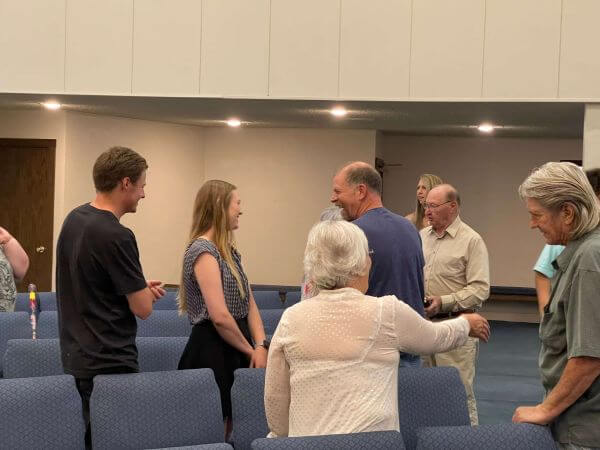 Group of adults talking to each other inside first southern baptist church